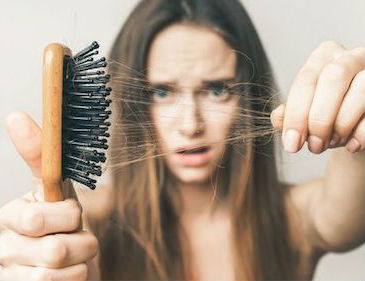 Girl pulling hair out of brush hair loss